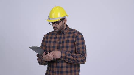 pensando : Young bearded Indian man construction worker reading on clipboard