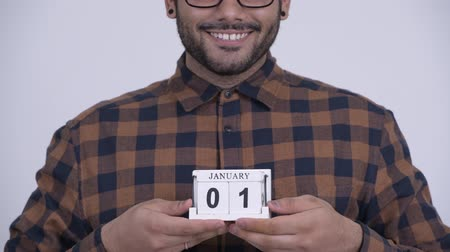 Happy young bearded Indian hipster man holding calendar block ready for New Years