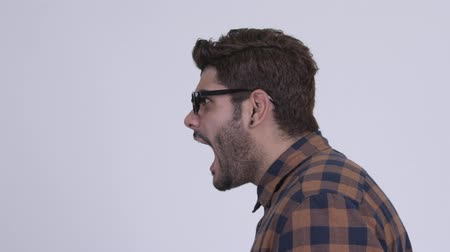 Profile view of angry young bearded Indian hipster man shouting and screaming