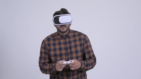Young bearded Indian hipster man playing games and using virtual reality headset Wideo
