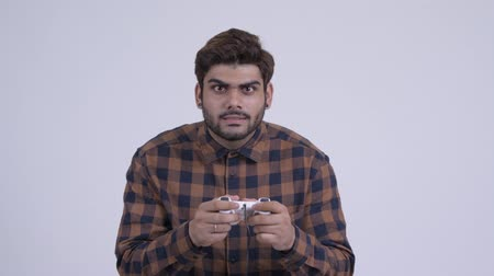 Young bearded Indian hipster man playing games