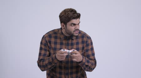 Stressed young bearded Indian hipster man playing games and losing