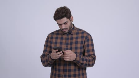 Young bearded Indian hipster man thinking and using phone Wideo