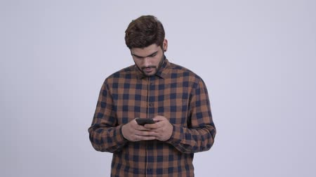 Happy young bearded Indian hipster man using phone