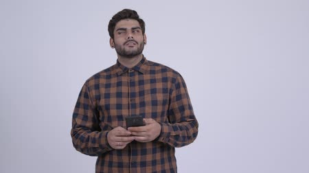 Happy young bearded Indian hipster man thinking and using phone