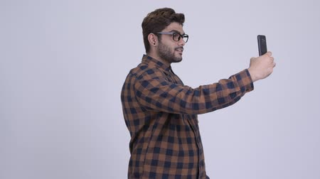 Happy young bearded Indian hipster man taking selfie with phone