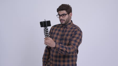 Young bearded Indian hipster man vlogging with phone