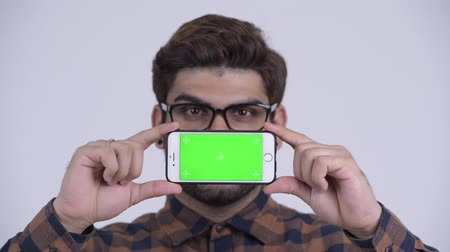 Face of happy young bearded Indian hipster man showing phone