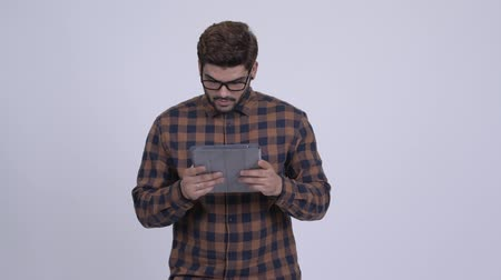 Young bearded Indian hipster man using digital tablet