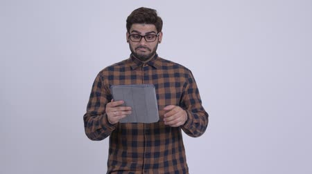 Happy young bearded Indian hipster man using digital tablet