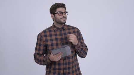 Happy young bearded Indian hipster man thinking while using digital tablet Wideo