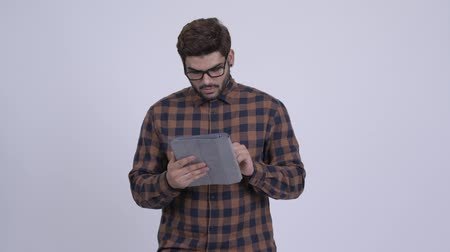 Young bearded Indian hipster man thinking while using digital tablet Wideo