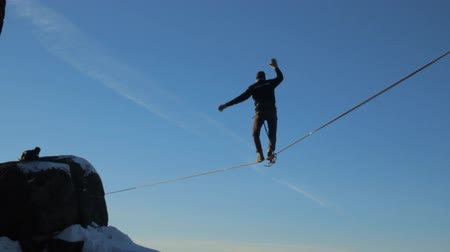 tightrope : Ropewalker poised over the abyss.