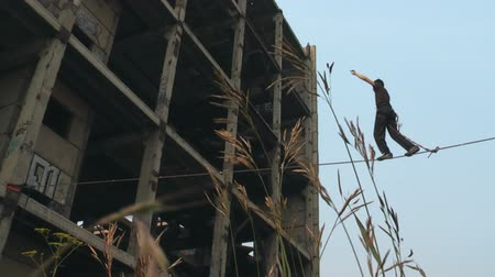 tightrope : A man walks on a rope at a height on an abandoned construction site. Stock Footage