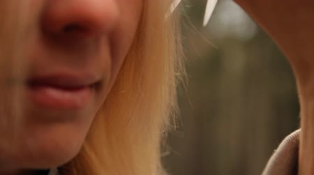 prádelník : Close-up of the lips and hair of a young woman while cutting outdoors. Slow motion shot.