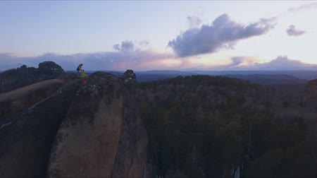 élénk : Aerial shot of the Barber makes the cut in the open air at sunset. Extreme haircut on the top of the rock in the Siberian nature reserve Stolby.
