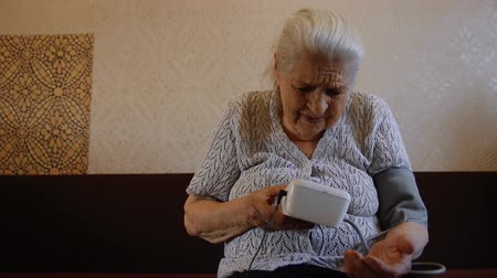nadciśnienie : An old woman is measuring her blood pressure. Grandmas using a tonometer.