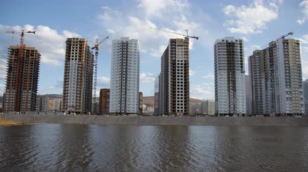 строительные леса : Time lapse of construction of a new district by the river.