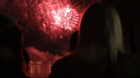 glow pyrotechnics : Silhouettes of women standing on the Bank of the river and looking at the fireworks.