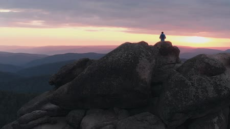 peak : Drone shot of lonely man standing on top of a mountain and enjoying the sunset