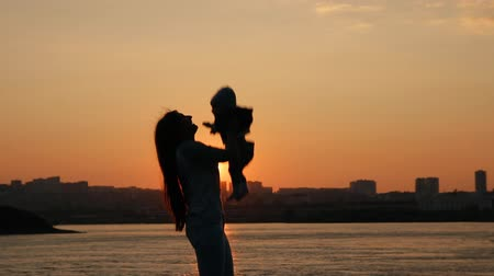 throws : A young mother cheerfully throws up her little son. Mother and child having fun walking by the river at sunset.