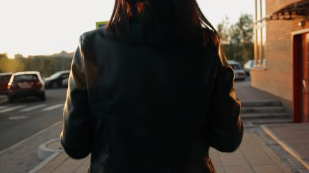 umutlu : A young woman walks the streets of the city at sunset.