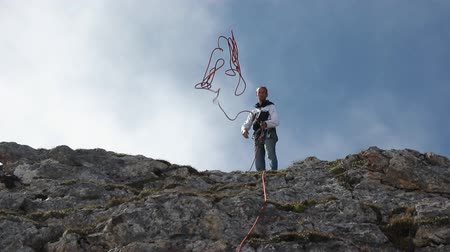 riskli : Slow motion of a climber throws a rope while standing on top of a mountain.