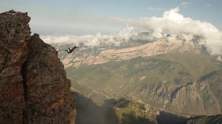 abyss : Brave man jumping off a cliff, rope jumping in the mountains. Stock Footage
