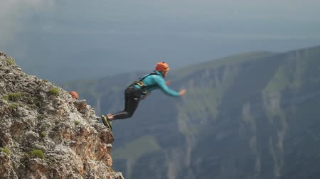 vysoký : Man jumping off a cliff, rope jumping in the mountains.