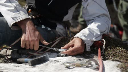 clamp : Close-up of the mans hand twisting the key bolt into the rock. Organization of insurance for rescue work. Stock Footage