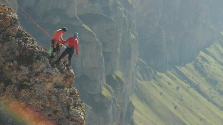 dangle : A group of climbers discussing a plan of action standing on the edge of the cliff. Stock Footage