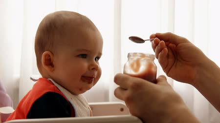 puericultura : Slow motion of a young happy father feeds his son baby fruit puree. Vídeos