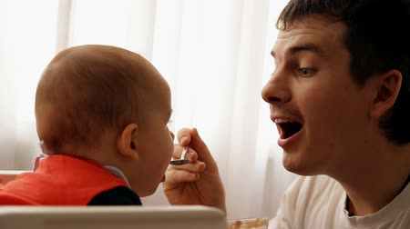 pai : Slow motion of a young happy father feeds his son baby porridge.
