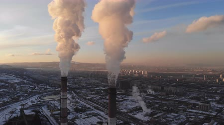carbon dioxide : Aerial view of smoke rising from the chimney of a coal boiler. Top-down movement with camera rotation.