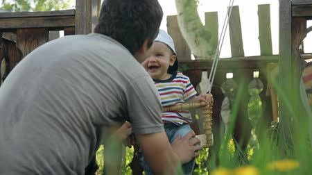 otec : Slow motion of father swings his happy little son. Dostupné videozáznamy