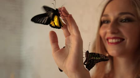 kırılganlık : Young charming woman smiling looking at live butterflies on her hand.