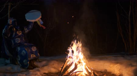 культ : The shaman beats his drum sitting near the fire. Стоковые видеозаписи