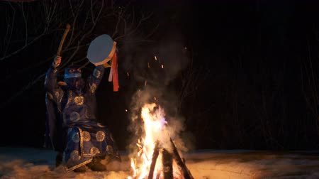 посвящение : The shaman is sitting by the fire and sways, holding a tambourine in his hand.