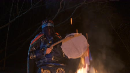 культ : The shaman is sitting around the fire and makes a magical ritual.
