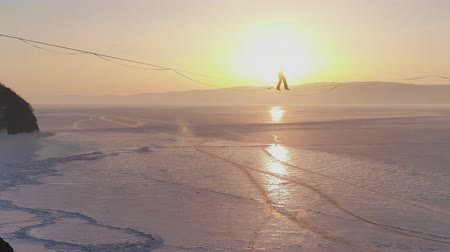 sıkı : The tightrope Walker is balancing on a rope between two rocks above a frozen lake.