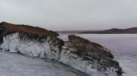 rampouch : Rocks covered with ice over a frozen lake.