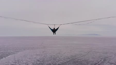 Silhouette of a man in a hammock mounted at high altitude.