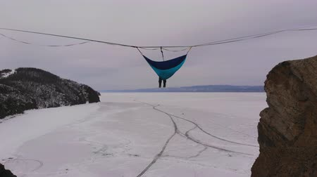 Man hanging in hammock above by ice of frozen lake Baikal.