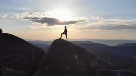 wspinaczka : The silhouette of a man standing triumphantly on a mountain top at sunset. Wideo