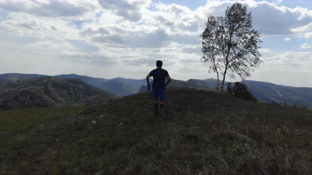 Athlete running on a mountain trail. Skyrunner trains outdoors. Стоковые видеозаписи