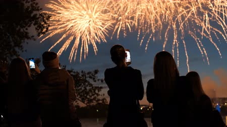 A crowd of people watching fireworks and shooting on a smartphone.