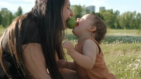 A young mother and her son eat an Apple. A small child bites an Apple. Стоковые видеозаписи