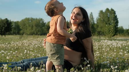 Young attractive woman and her son are laughing sitting in on the grass in the Park.