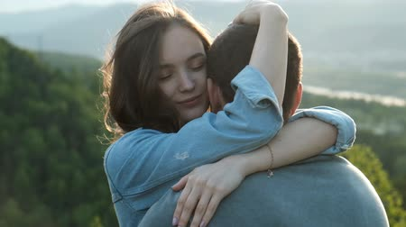 Slow motion of a young woman gently hugs her boyfriend at sunset.