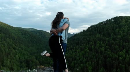 A young woman happily hugs her boyfriend standing on top of a mountain. 動画素材